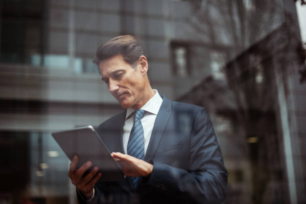 German businessman A formally dressed 55-year-old businessman is holding a digital tablet next to the window of the bright office. georgijevic frankfurt stock pictures, royalty-free photos & images