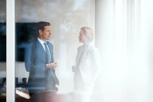 German Businesspeople Two formally dressed executives are talking in the bright office. georgijevic frankfurt stock pictures, royalty-free photos & images