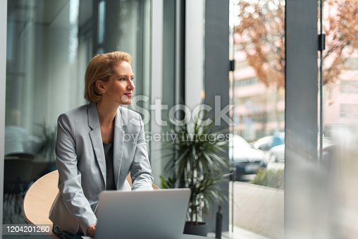 Formally dressed 40-year-old businesswoman is working on a laptop in office.