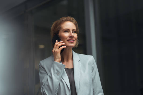 German businesswoman 40-year-old satisfied caucasian businesswoman is standing in office and using smartphone. georgijevic frankfurt stock pictures, royalty-free photos & images