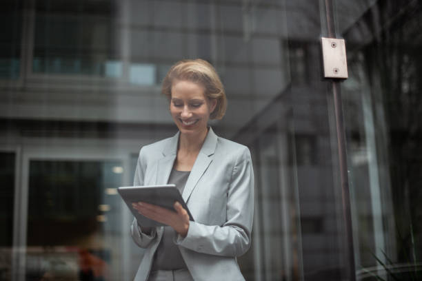 German businesswoman 40-year-old satisfied caucasian businesswoman is standing in office. georgijevic frankfurt stock pictures, royalty-free photos & images