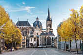Huge gothic cathedral in Aachen Germany during autumn with yellow trees at Katschhof against blue sky in the background