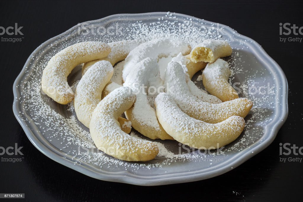 German Christmas pastries: vanilla crescent vanillekipferl on grey plate. Black wooden background. Top view. Christmas concept. stock photo
