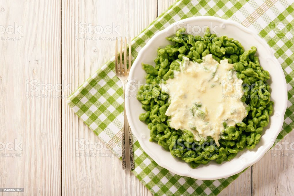 German dumplings (spaetzle) with spinach and cheese sauce. stock photo