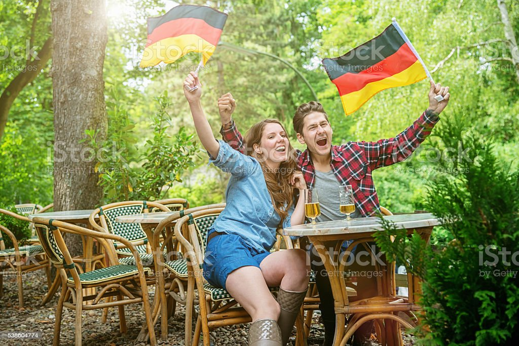 German Fan Couple Supporting Soccer Team in Beer Garden stock photo