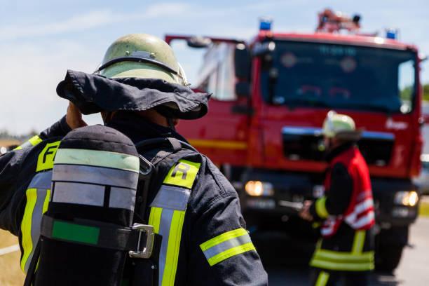 alemán bomberos (feuerwehr) está parado cerca de un accidente - bombero fotografías e imágenes de stock
