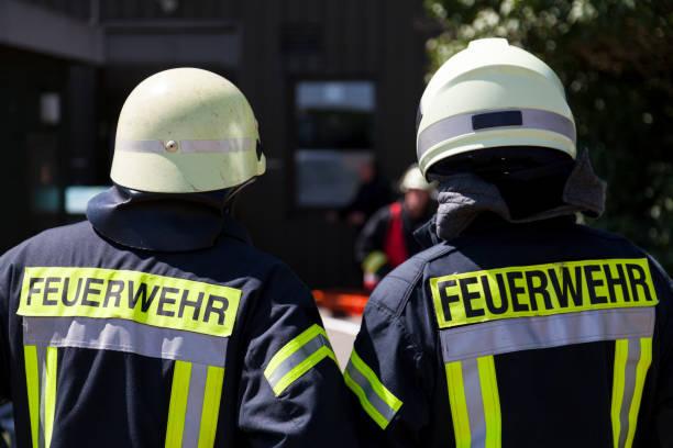 deutsche feuerwehr (feuerwehr) steht in der nähe eines unfalls - feuerwehrmann deutsch stock-fotos und bilder