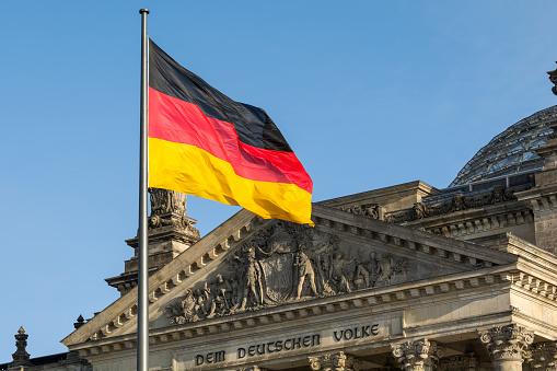 German flag fluttering front of Reichstag building. Berlin, Germany