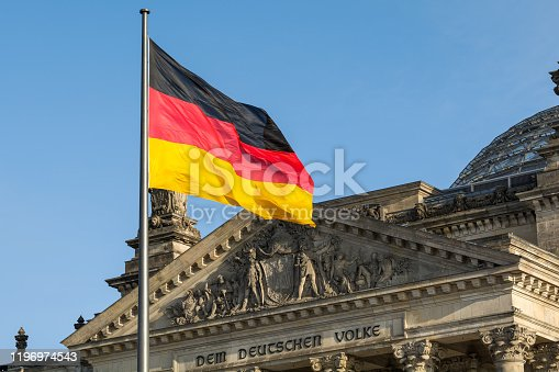istock German flag fluttering front of Reichstag building. Berlin, Germany 1196974543