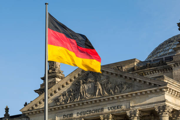 German flag fluttering front of Reichstag building. Berlin, Germany German flag fluttering front of Reichstag building. Berlin, Germany germany stock pictures, royalty-free photos & images