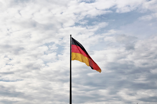 German flag waves with cloudy sky background