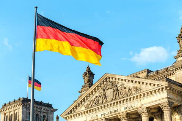 deutsche flaggen schwenken am berühmten reichstagsgebäude, sitz des deutschen bundestages, politik und tourismuskonzept - berlin mitte stock-fotos und bilder