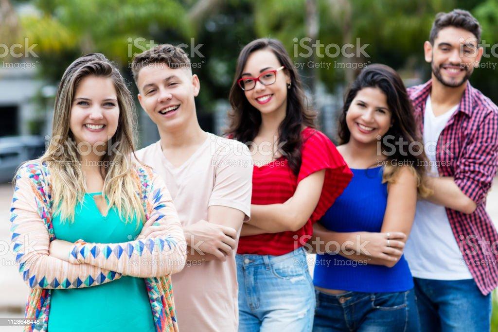 Chica alemana con jóvenes hombres y mujeres en línea - foto de stock