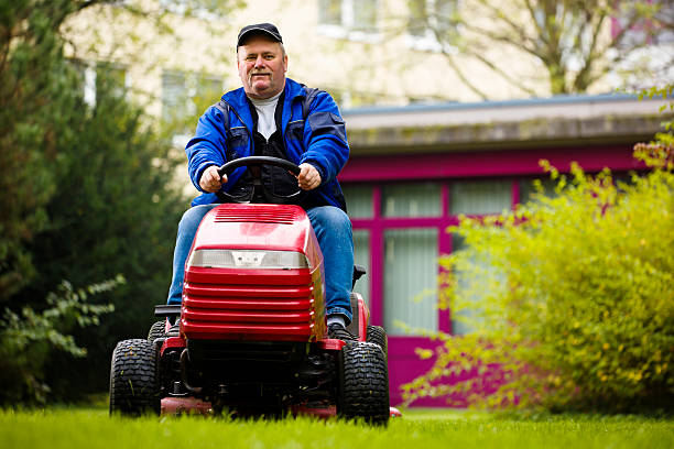 german landscaper on a riding mower - riding lawn mower stock photos and pictures