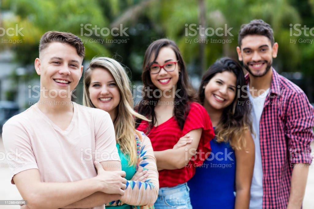 Hombre alemán con jóvenes hombres y mujeres en línea - foto de stock