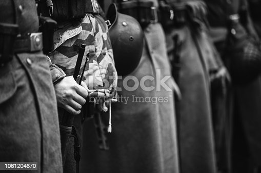 1061204700 istock photo German Military Ammunition Of A German Soldier. Unidentified Re-enactors Dressed As World War Ii German Soldiers Standing Order. Photo In Black And White Colors. Soldiers Holding Weapon 1061204670