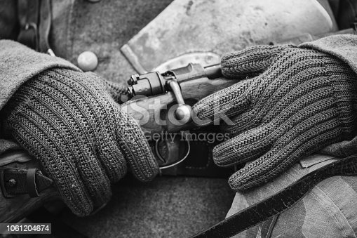 1061204700 istock photo German Military Ammunition Of A German Wehrmacht Soldier At World War II. Warm Autumn Clothes, Soldier's Overcoat, Gloves, Helmet, Sapper Shovel, Rifle. Photo In Black And White Colors. 1061204674