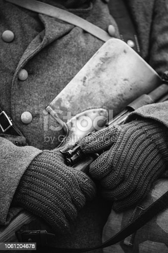 1061204700 istock photo German Military Ammunition Of A German Wehrmacht Soldier At World War II. Warm Autumn Clothes, Soldier's Overcoat, Gloves, Helmet, Sapper Shovel, Rifle. Photo In Black And White Colors. 1061204678