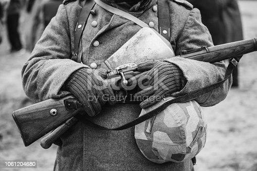 1061204700 istock photo German Military Ammunition Of A German Wehrmacht Soldier At World War II. Warm Autumn Clothes, Soldier's Overcoat, Gloves, Helmet, Sapper Shovel, Rifle. Photo In Black And White Colors. 1061204680