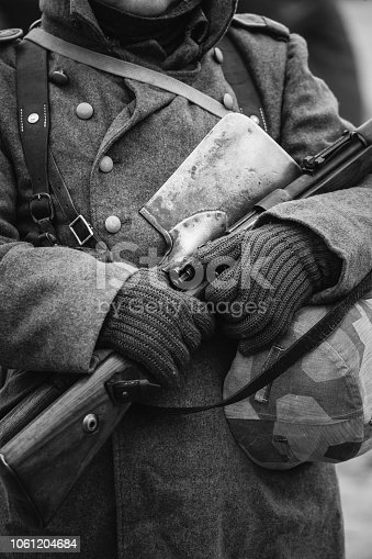 1061204700 istock photo German Military Ammunition Of A German Wehrmacht Soldier At World War II. Warm Autumn Clothes, Soldier's Overcoat, Gloves, Helmet, Sapper Shovel, Rifle. Photo In Black And White Colors. 1061204684