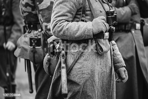 1061204700 istock photo German Military Ammunition Of A German Wehrmacht Soldier At World War II. Warm Autumn Clothes, Soldier's Overcoat, Gloves, Helmet, Pouch, Sapper Shovel, Flask, Rifle. Photo In Black And White Colors. 1061204698