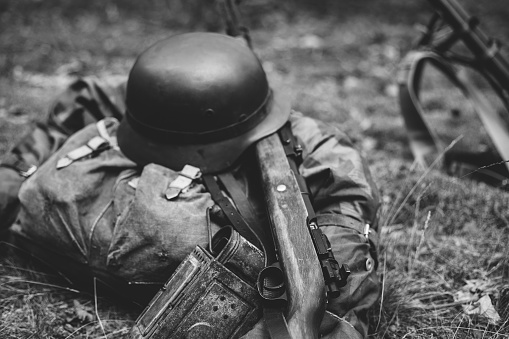 istock German Military Ammunition Of World War Ii On Ground. Military Helmet, Lights, Rifle. Photo In Black And White Colors 1056037176