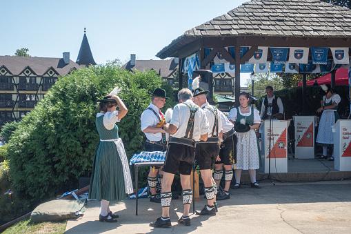 German musical band wearing traditional bavarian costumes preparing to Oktoberfest performance.