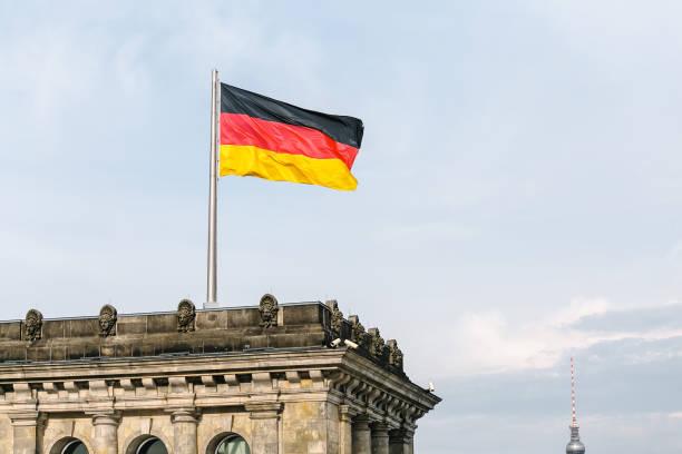 deutsche nationalflagge beim regierungsgebäude des bundestags in berlin - spielerfrauen stock-fotos und bilder