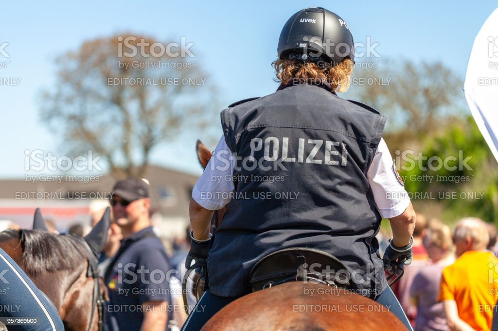German police horsewoman rides on a police horse for training exercise in a crowd. The german word Polizei means police. stock photo