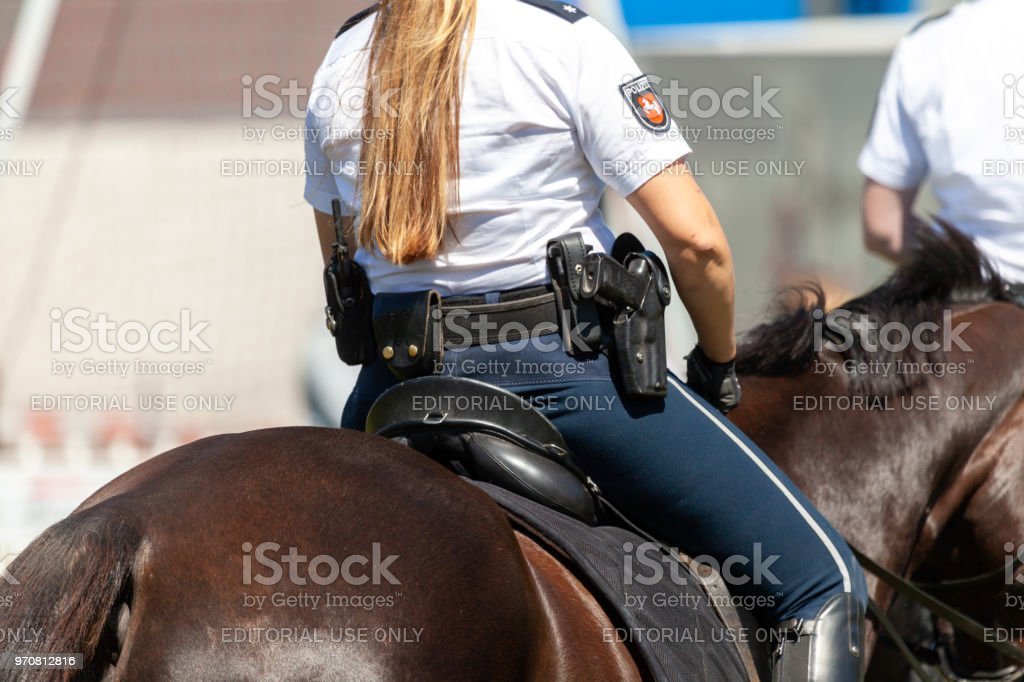 German police horsewoman rides on a police horse for training exercise in a crowd. stock photo