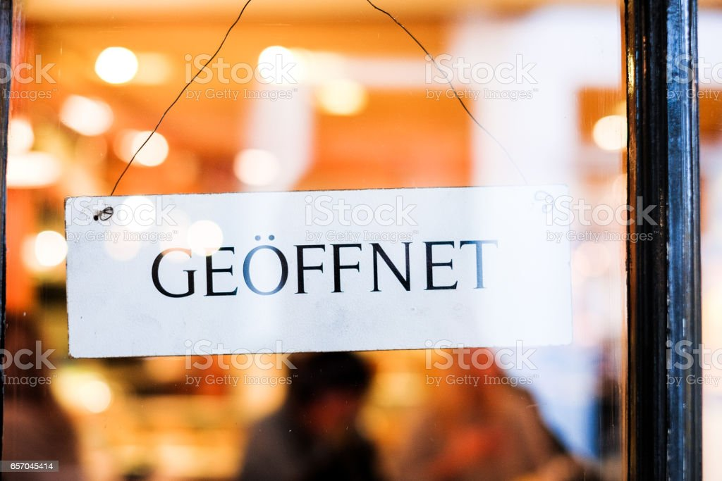 German sign in door saying Geoffnet, meaning 'open' - foto stock