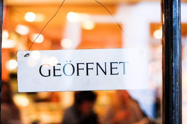 German sign in door saying Geoffnet, meaning 'open' - foto stock