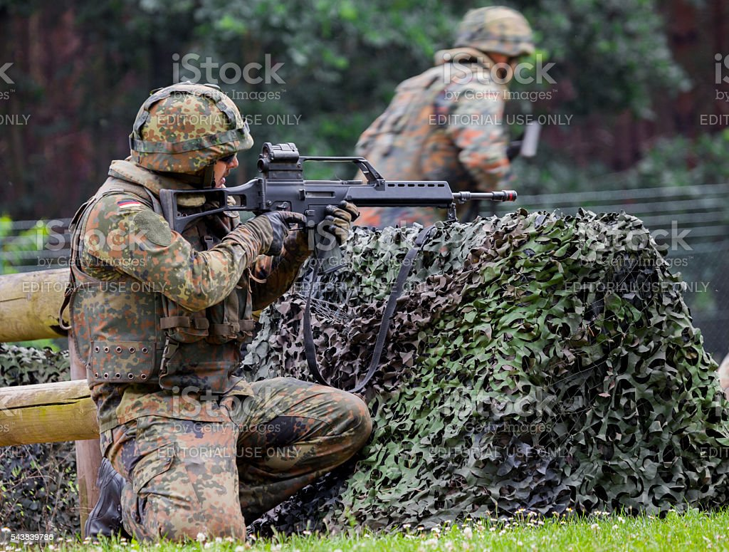 german soldier fires with hk g 36 rifle stock photo