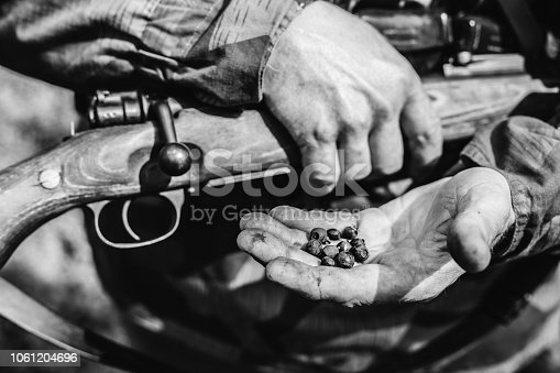 1143756392 istock photo German Soldier Holding Holding A Rifle And Blackberries On Hand. Photo In Black And White Colors 1061204696
