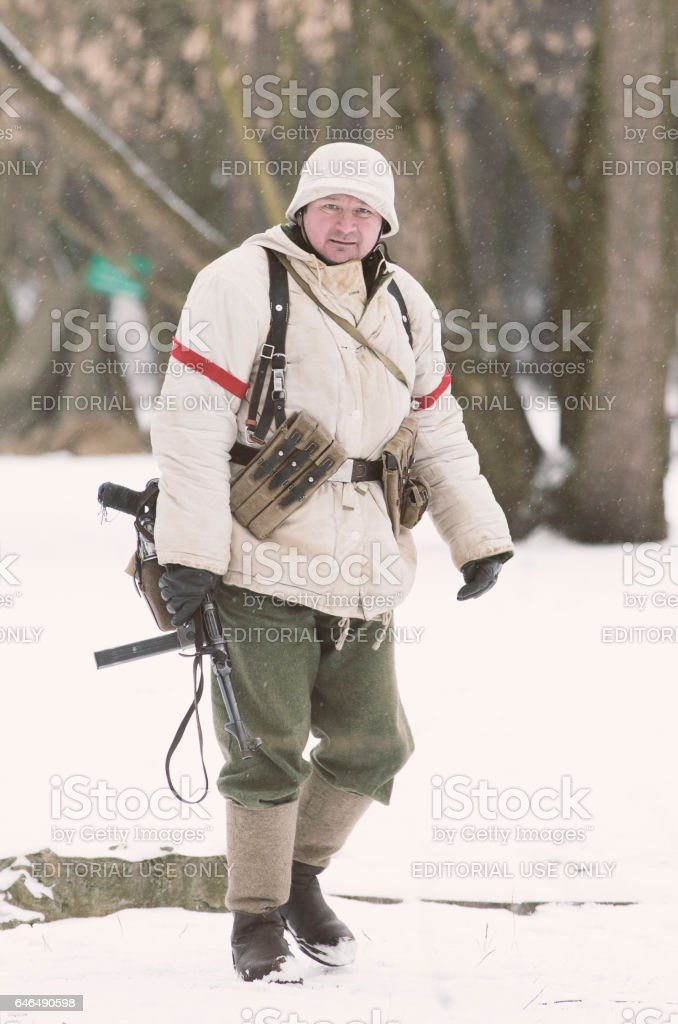 German soldier in winter camouflage with a gun, MP-40 in hand stands on position. stock photo