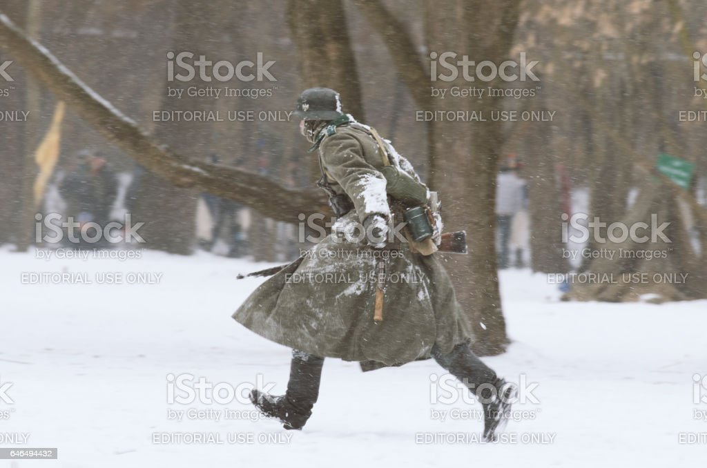 German soldier running with rifle at the ready during a snowfall. stock photo