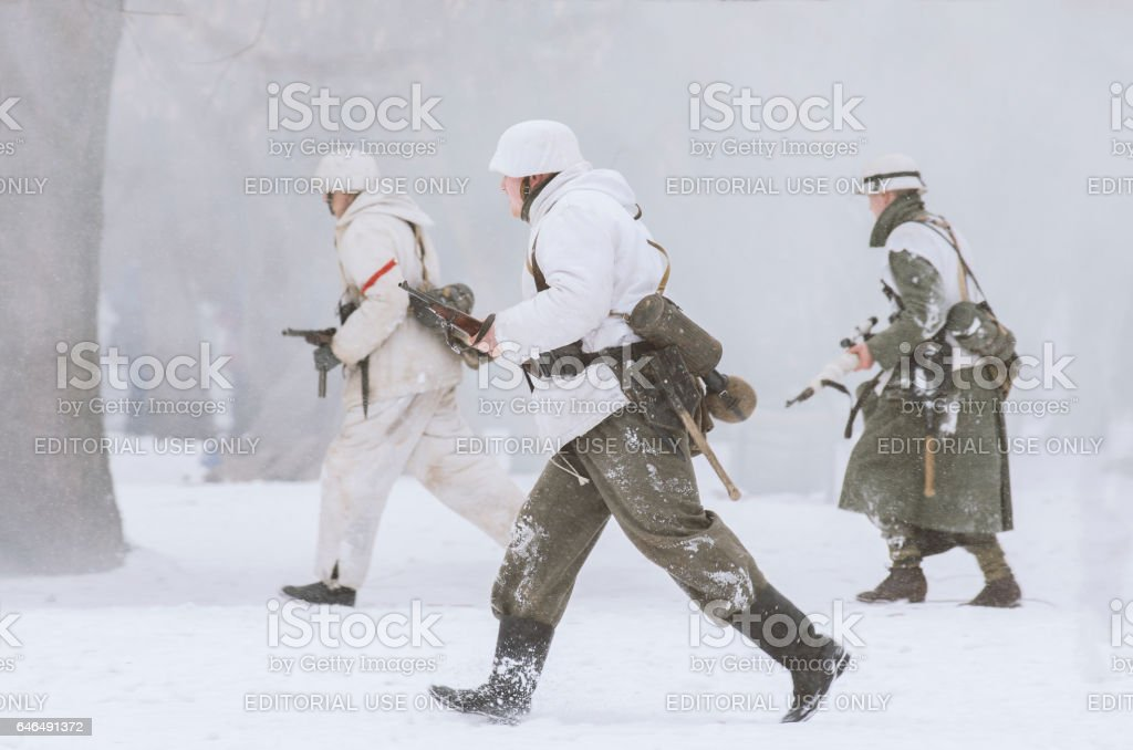 German soldiers with weapons at the ready in the snowy haze fleeing the attack. stock photo