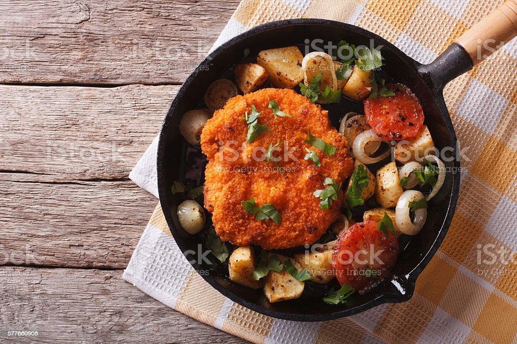 German Weiner schnitzel with vegetables in pan. horizontal top view stock photo
