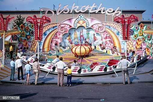 Berlin, Germany, 1968. German-American folk festival in Berlin (West). Visitors to the amusement park are standing in front of a gondola carousel called Discotheque.