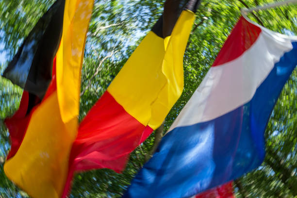 German-Dutch-Belgian border at tri-border region in Aachen Germany with waggling flags stock photo