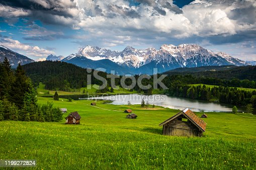 Idyllic mountain landscape in the Allgäu region of Bavaria in Germany. Beautiful cumulus clouds in the summer sky. Small log cabins surrounded by a green pasture in the foreground. Lake Geroldsee and Karwendel Mountains in the Background. Germany - Europe