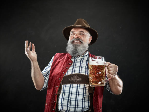 germany, bavaria, upper bavaria, man with beer dressed in in traditional austrian or bavarian costume - baviera foto e immagini stock