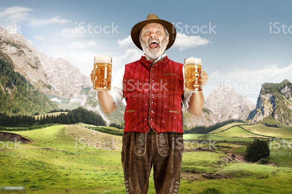 Duitsland, Beieren, Opper-Beieren, man met bier gekleed in traditionele Oostenrijkse of Beierse kostuum - Royalty-free Actieve ouderen Stockfoto