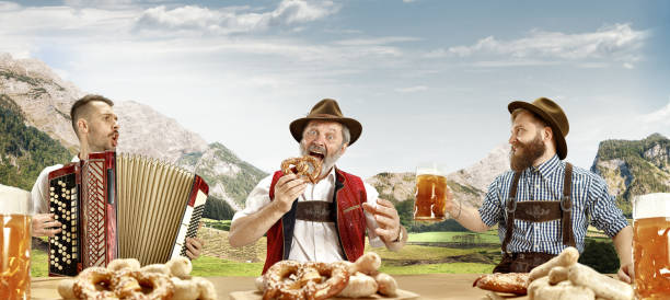 germany, bavaria, upper bavaria, men with beer dressed in traditional austrian or bavarian costume - oktoberfest stock photos and pictures