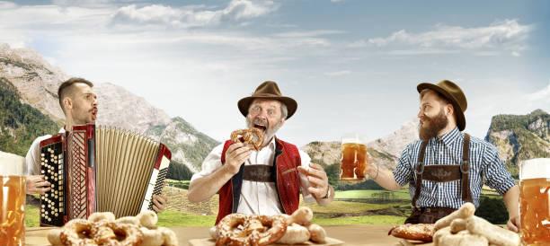 alemania, baviera, baviera superior, hombres con cerveza vestida en traje tradicional bávaro o austríaco - oktoberfest fotografías e imágenes de stock