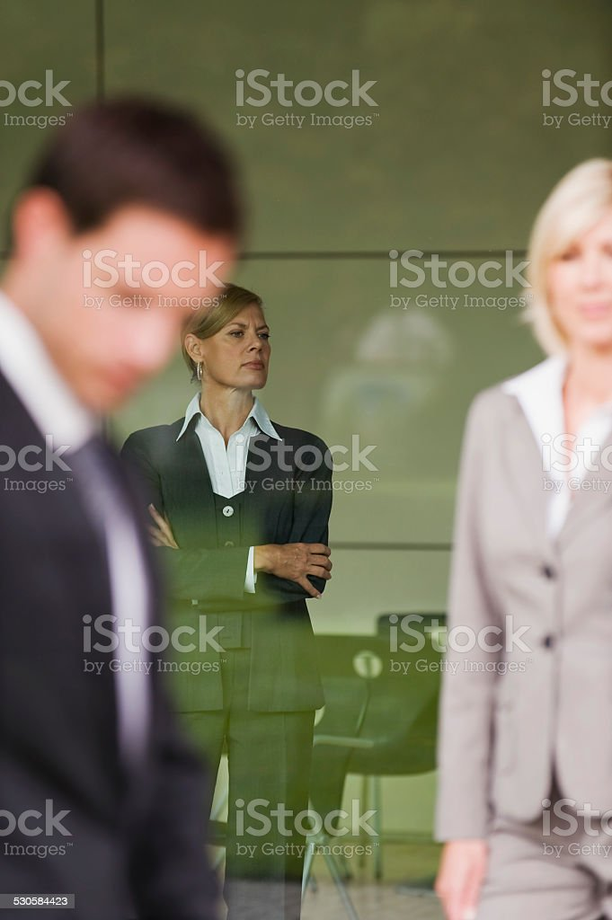 Germany, business people, woman with arms crossed in background stock photo