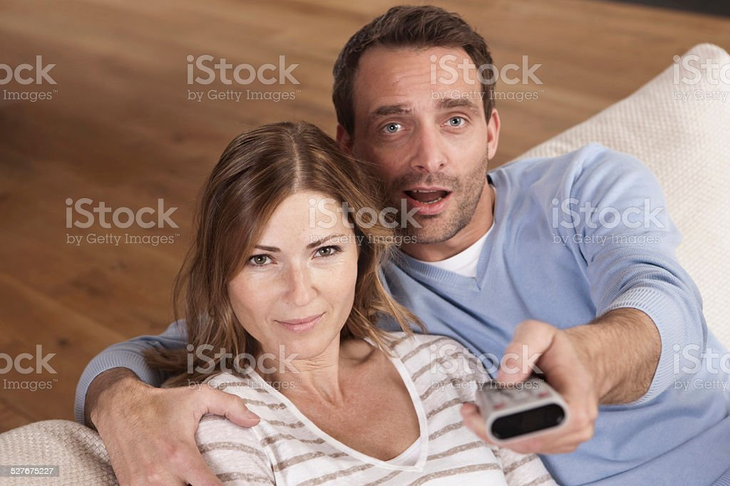 Germany, Couple sitting on couch with man holding remote control stock photo