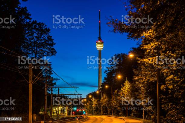 Photo of Germany, Empty street alongside railway leading to famous television tower of stuttgart city, called fernsehturm by night in magical twilight atmosphere