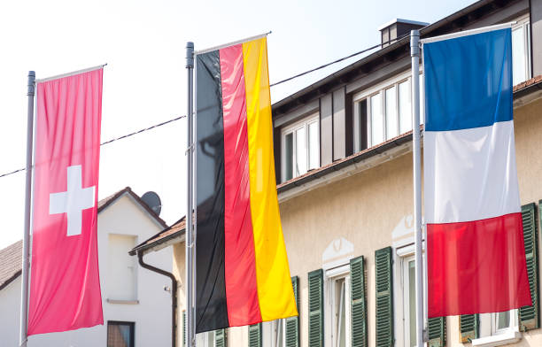 Germany flag, Swiss flag, French flag blowing in the wind (border triangle) stock photo