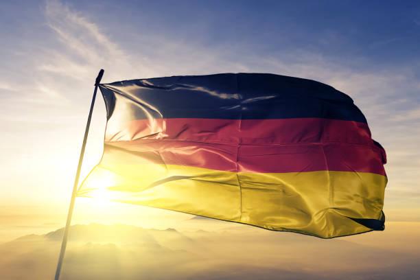 alemania bandera alemana paño tela ondeando en la niebla de la niebla de amanecer superior - alemania fotografías e imágenes de stock